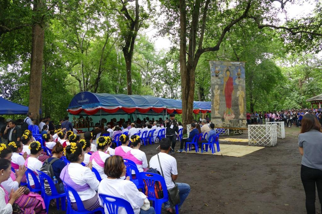 Im Hintergrund ist das Bild Buddahs zu sehen. Zur freundlichen Ermahnung an das Versprechen schaukelt es an einem dicken Ast.
